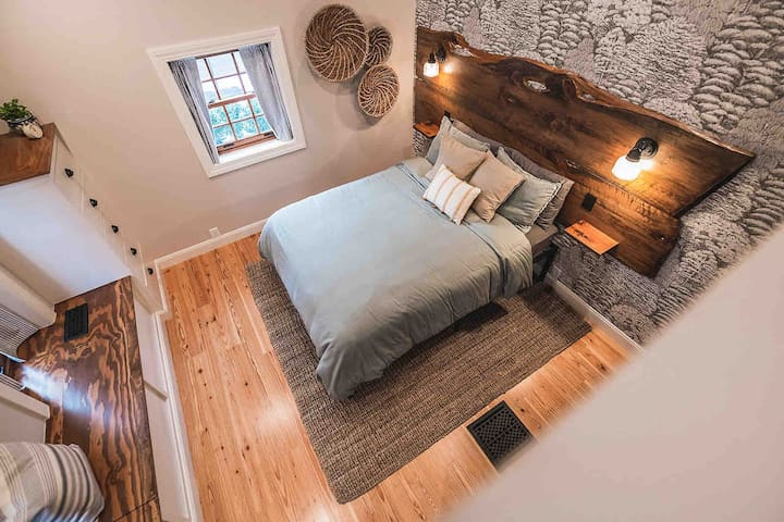 Heading up the wide stairs to the second floor you will find a spacious and beautifully designed bedroom. Calming wallpaper, exposed brick, wooden beams and natural sunlight will have you relaxing in bed all day.