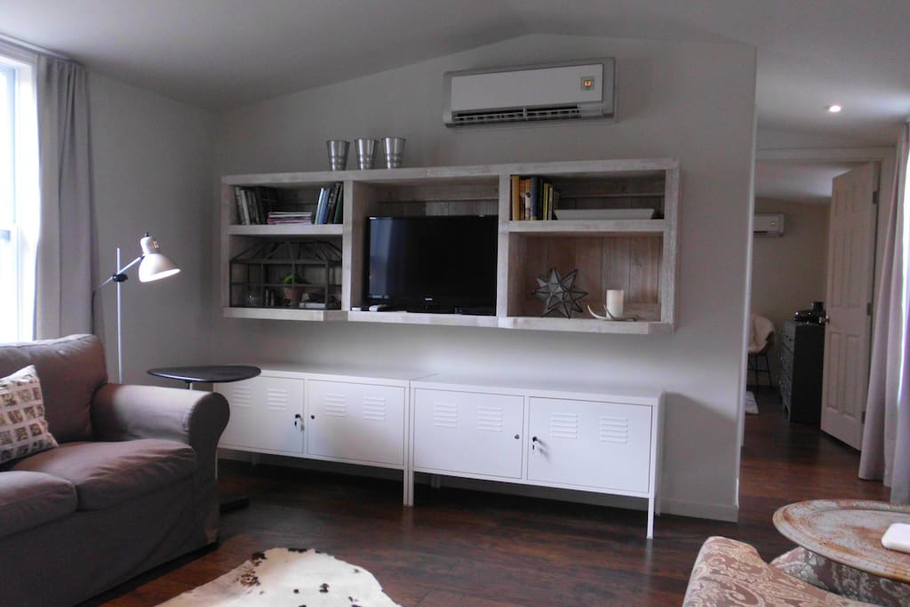 Living room with wall mounted DirecTV and WiFi.  Ductless H/AC unit visible above.