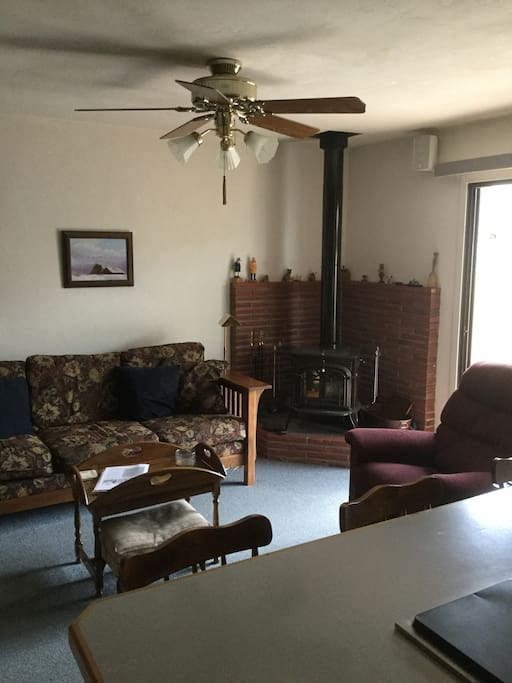 Family room with wood-burning stove, tv, breakfast bar, view of garden.