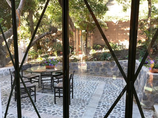 The kitchen door opens on a lovely patio and garden, with a table, orchids and fresh herbs
