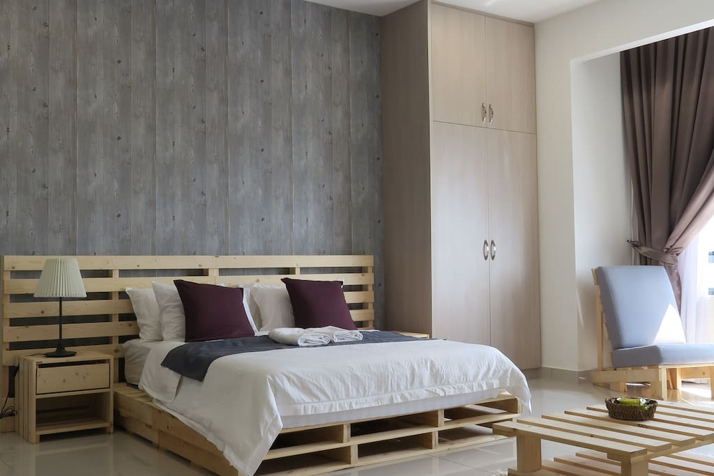1 queen size bed with a wooden wardrobe next to it.