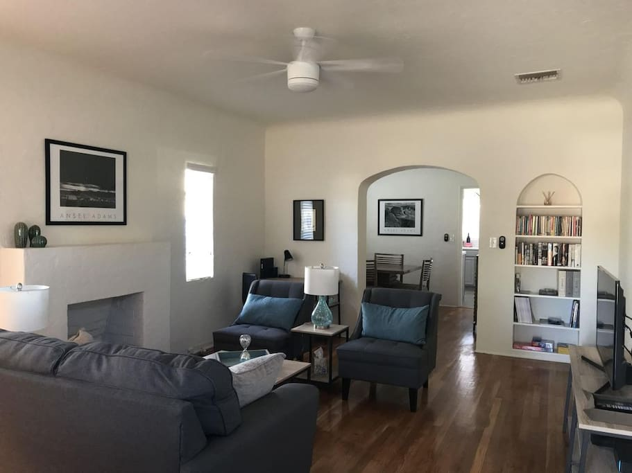 Living room with comfortable seating, reading material, desk and television.