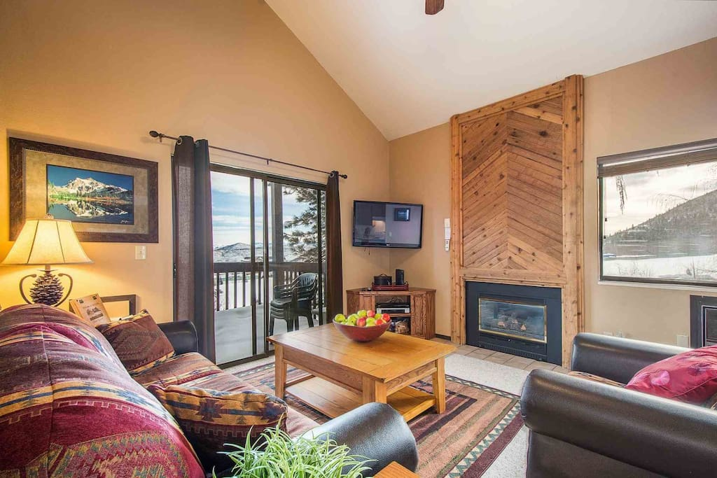 """The living room features a large living area with plush leather furniture, gas fireplace, a 42"""" HDTV and a sliding glass door to access your balcony."""