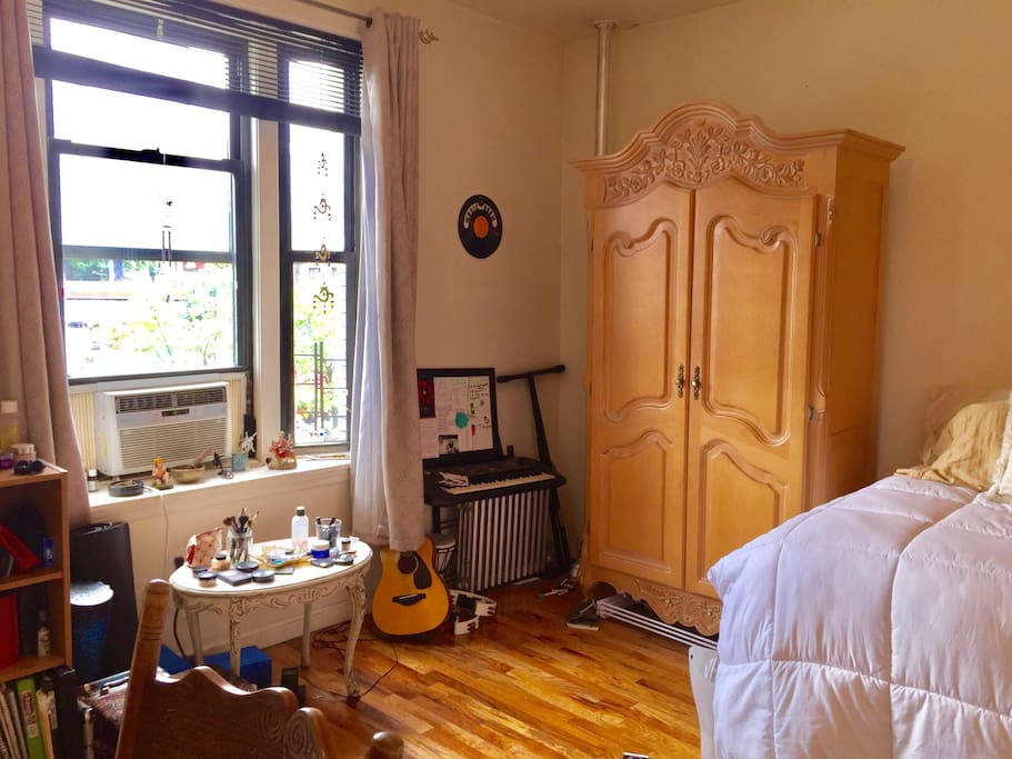 My (large) room, which is the current one being rented. The bed is pillow-topped, full-sized, and extremely comfortable. It is facing a large bay window which projects tons of natural light, but also has black out curtains so that the light doesn't wake you up in the morning. There's also a small keyboard that you're welcome to use. And there's also a window AC, and a large, powerful fan. The dresser next to the bed will have 1/2 of the drawers emptied out so that you can use them.