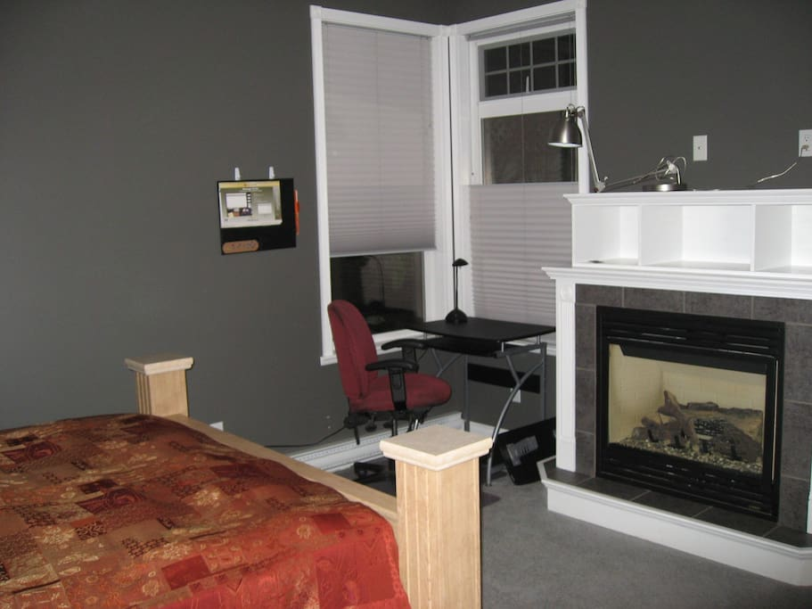 Computer desk with chair by the window and fireplace