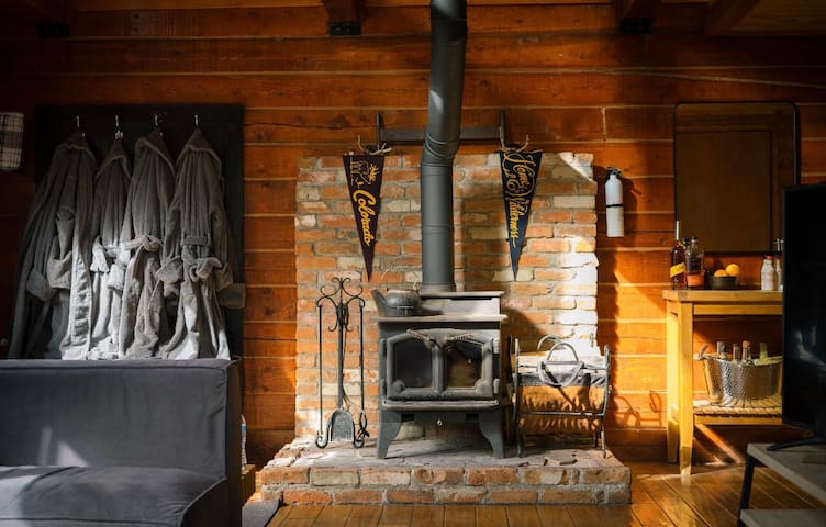 The cabin has all the ingredients for a cozy night in: terrycloth robes for the hot tub, a potbelly stove for a wood-burning fire and an old-fashioned bar for the perfect cabin cocktail.