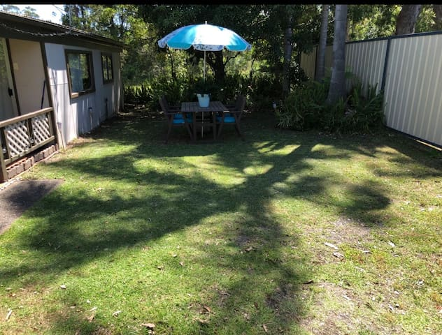 Outdoor table and yard to enjoy bbq drinks and kids to relax and play in