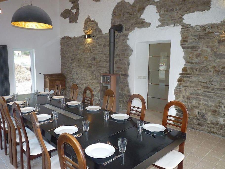 Esszimmmer mit 5m hoher Natursteinmauer und Designer-Lampen