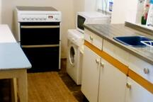 Kitchen with electric oven, microwave, compact washing machine, kettle, toaster, pantry