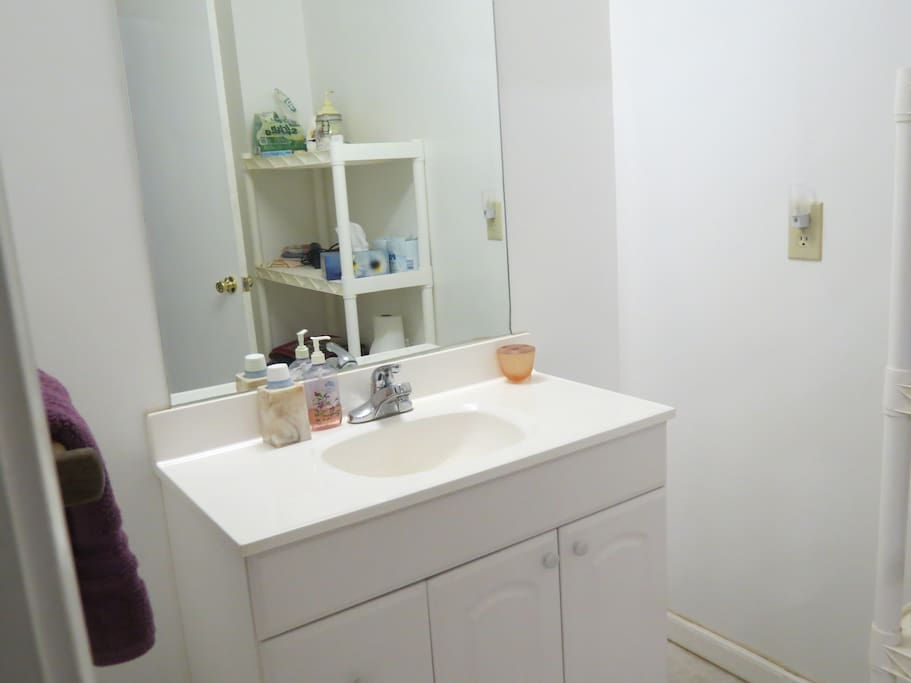 Bathroom sink separated by door from toilet and shower.