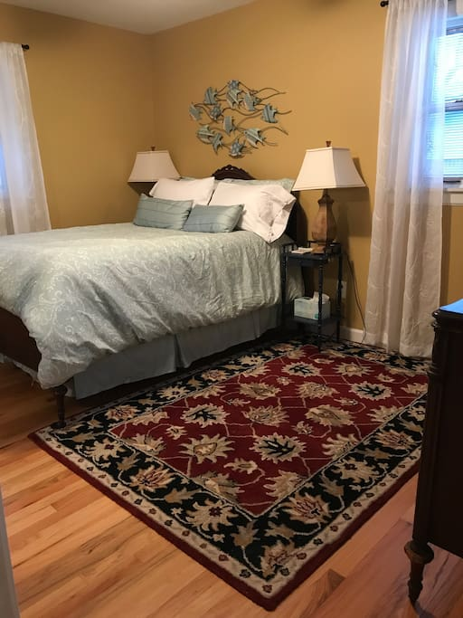 Comfortable double bed with two windows letting in natural light