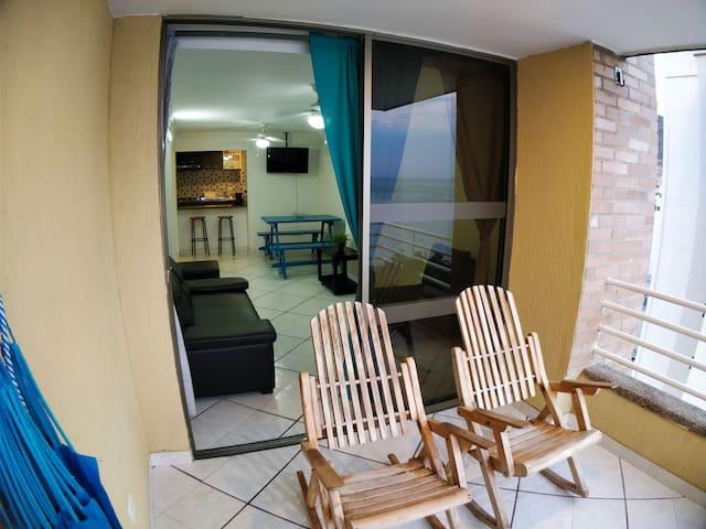 Balcón del apartamento con hamaca y sillas de madera.