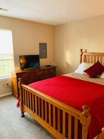 """Master bedroom with queen size bed, dresser, nightstand.  32"""" television with cable."""
