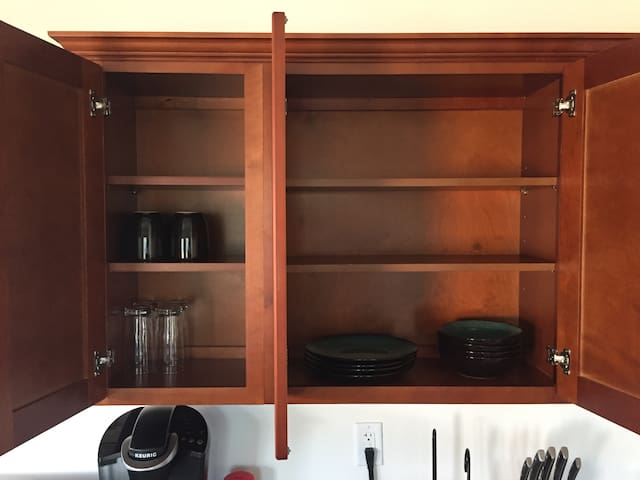 Coffee mugs, drinking glasses, plates and bowls are all there for your use. Silverware is located in the drawers below.