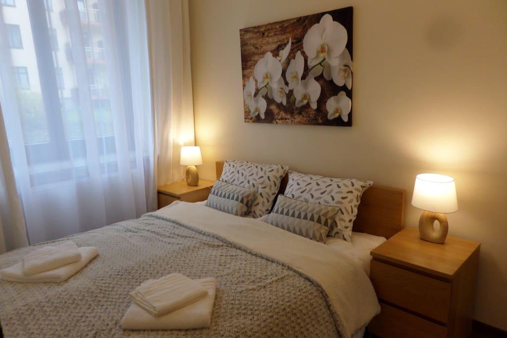 podwójne łóżko, pościel, okna z roletami zaciemniającymi