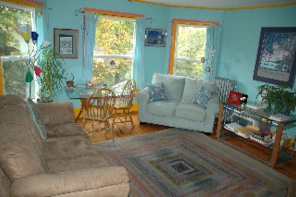 Living room with 3 bay windows, a couch and 2 loveseats, plus big screen TV (if you want it)