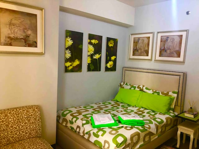 As shown inside the bedroom is cozy queensize bed available for a family of 3 with accent chair and paintings