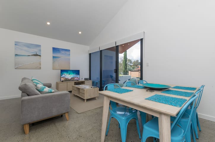 Combined spaces - kitchen, TV & dining area which leads out on to the front balcony through the sliding doors.