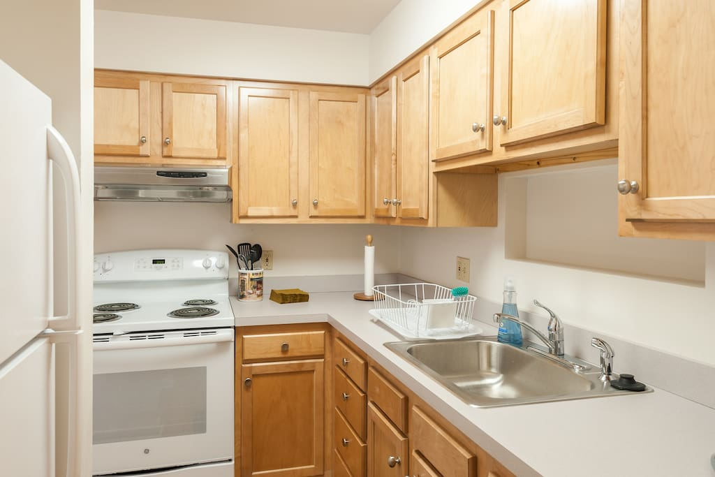 New kitchen with electric stove and full-size refrigerator