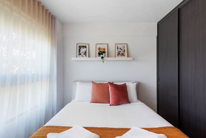The first light-filled queen bedroom is beautifully styled and features hotel quality linens for a good night's sleep.