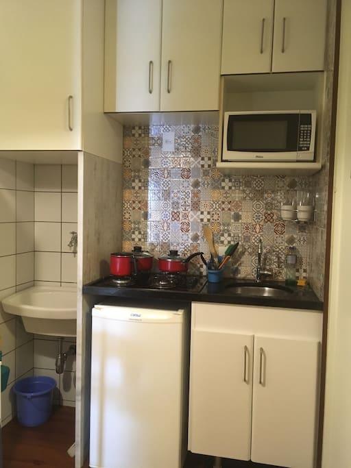 Espaço cozinha, frigô, microondas, tanque,armários.