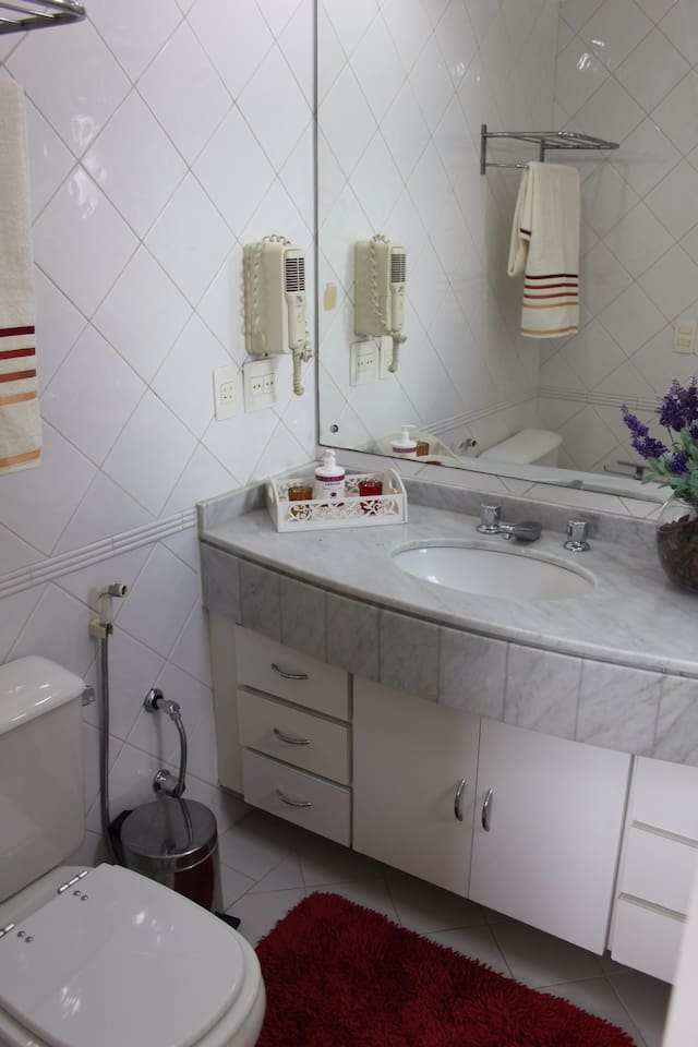 Banheiro com chuveirinho, secador de cabelos e conjuntos de toalhas. / Bathroom equipped with hairdryer and set of towels