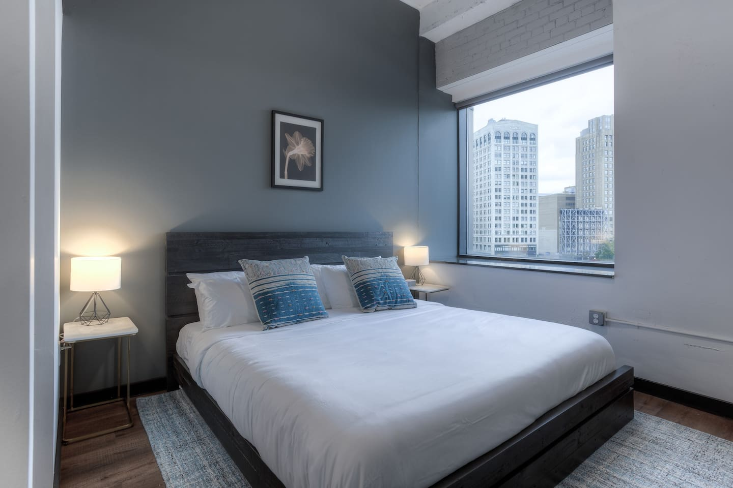 The master bedroom features a king bed with downtown city views