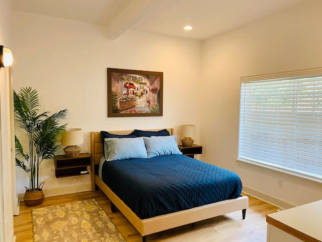 Second bedroom with comfortable Queen bed and bedside table outlets.