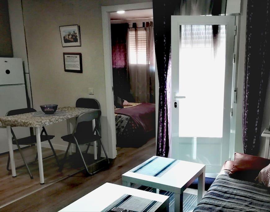habitación con cama de matrimonio, salón con sofá cama y la cocina americana.