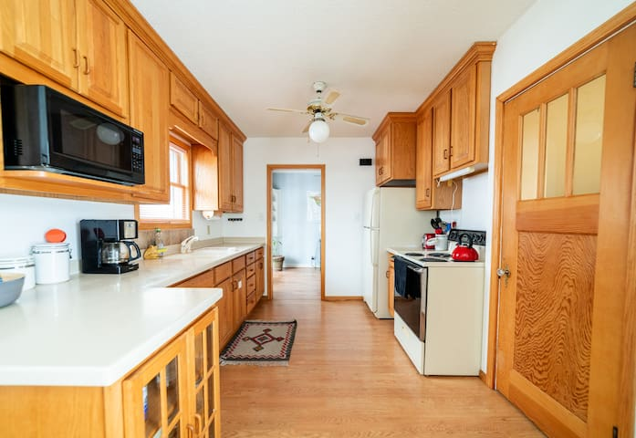 Shared kitchen with access to basic cooking supplies, dishes, and refrigerator space.
