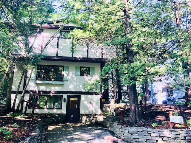 Roomy chalet style home on Elkhart Lake surrounded by trees  (driveway pictured is parking spot 1 of 3)