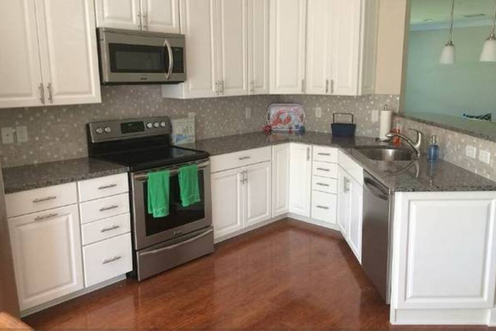 Both kitchens feature the same gorgeous white kitchen with stainless steel appliances and coastal backdrop. Comes with everything you need! (76 Pictured)