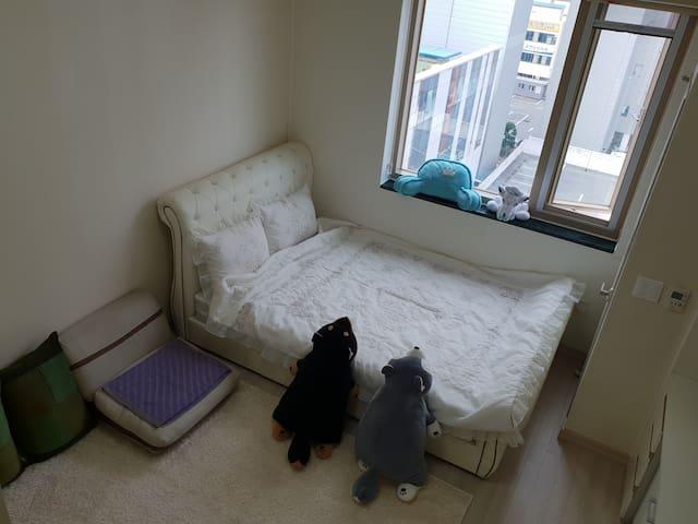 하얀 카페트와 올 컬러 화이트의 이불 배게 세트로 최고급 침대 와 침대로 변경가능한 1인 소파베드와 함께 존재함