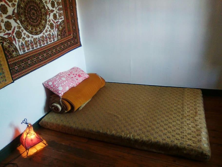 Cama doble estilo thai (sin somier) en habitación luminosa. La habitación tiene un pequeño escritorio.