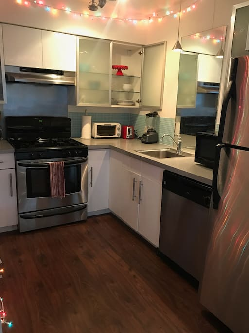 Kitchen features dishwasher, toaster, microwave, stove/oven, fridge, all dinnerware.