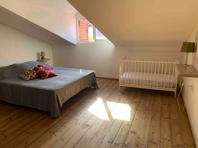 Chambre 2 côté bourg équipée d'un lit queen size (160) de la climatisation, d'un coin lavabo miroir étagère, d'un lit bébé et d'un espace penderie et étagères - accès direct à la douche et aux toilettes