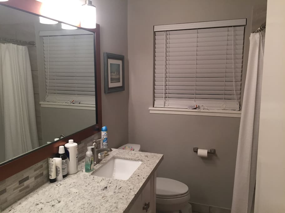 Shared bathroom with large vanity, shower with tub, and hairdryer, shampoo, conditioner, etc for your use - no need to bring travel size toiletries.