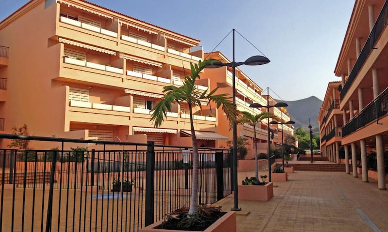 The apartment is located in the middle on the second floor (behind the leaf of the first palm tree), right next to the pool and at only 25m from the elevator/stairs