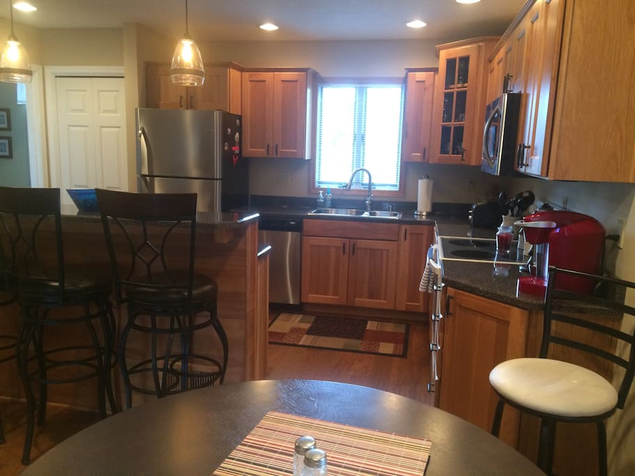 Kitchen remodeled a few years ago with new eating bar, birch wood cabinets, sink/faucet, refrigerator, microwave and counters.