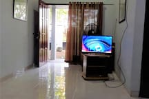 Ruang tengah dilengkapi TV dan kipas angin.  The living room is furnished with a TV and a fan.