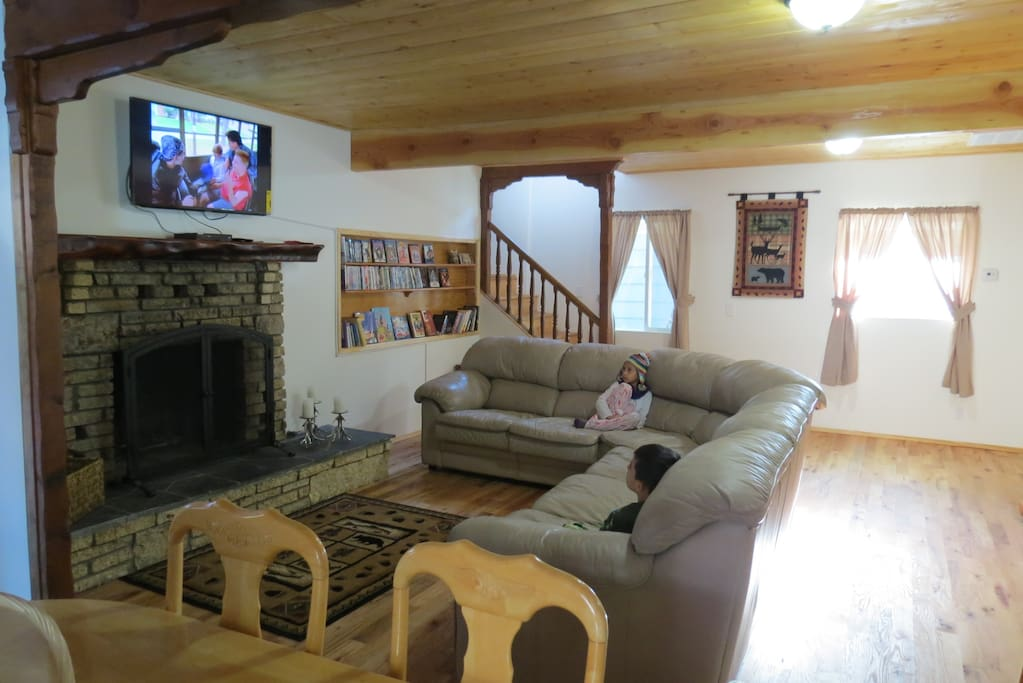 Large open living room with leather sectional. Solid oak floors and pine ceilings throughout cabin.