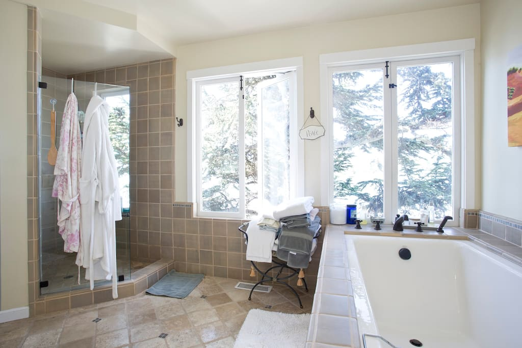 Master bath with large soaking tub and windows overlooking the water