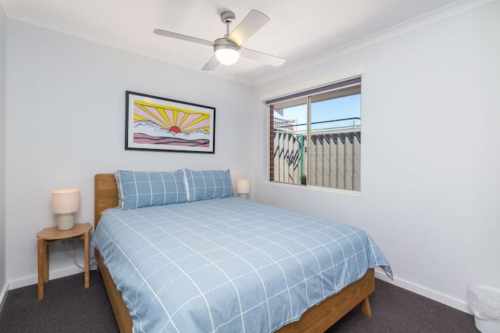 Bedroom two, Queen bed. Window looking out to the side area. Single robe for your belongings. Ceiling fan.