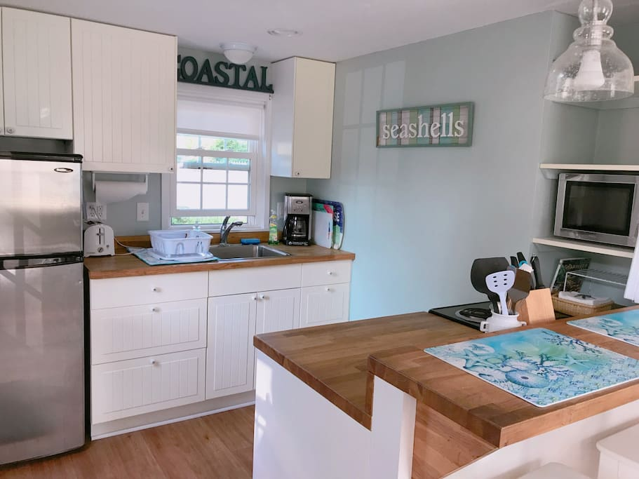 Kitchen with refrigerator, cooktop oven, microwave, toaster and coffee maker. Kitchen is fully stocked with all cookware and dining needs. Also counter seating area for two.
