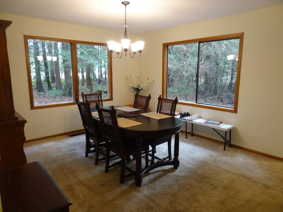 Dinning room with picture windows looking into forested surroundings.