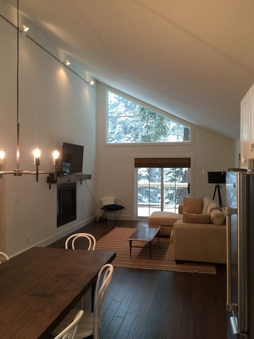 new flatscreen tv in light-filled living room opens to kitchen and deck