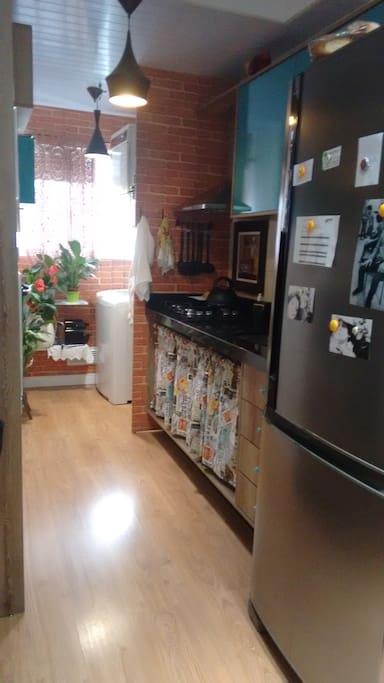 Cozinha com geladeira, microondas, forno, fogão e louças.