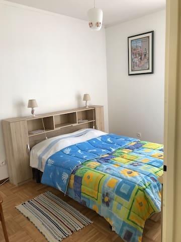 Chambre 1 avec un lit 2 personnes (140cm x 190cm), un placard et une  porte fenêtre équipée d'un volet roulant.