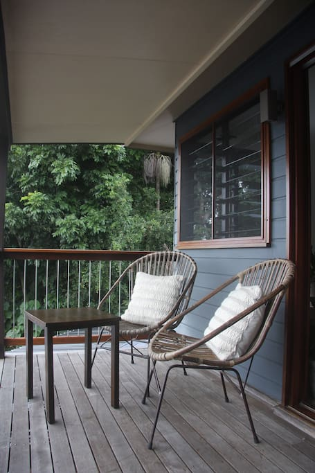 private balcony with view of stunning garden across the valley to byron bay lighthouse & ocean.