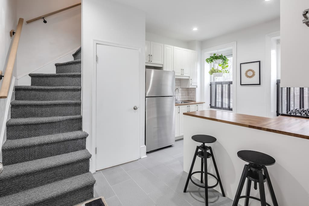 Fully equipped kitchen with barstool seating, stairs leading to living room/bathroom.